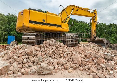Yellow belt excavator on heap of bricks of demolished house