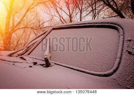 windshield of the old abandoned car covered with snow