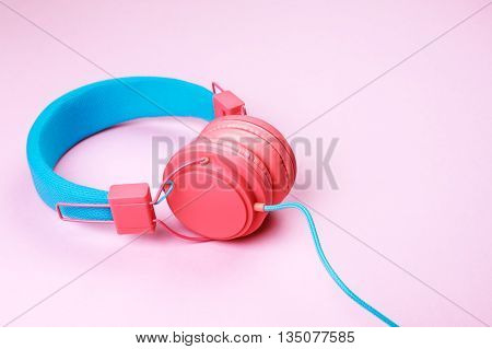 Pink and blue headphones on pink background. Place for text on it.