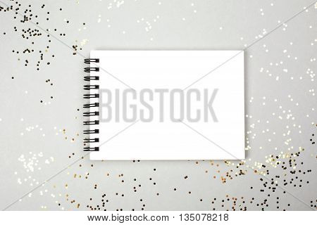 Paper note book with white pages lying on festive background with little golden sparkles. Place for text.
