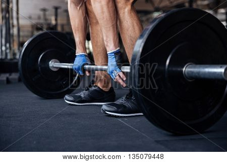 Cropped image of a muscular fitness man lifting heavy barbell at the gym