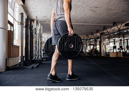 Young handsome bodybuilder man prepare to do exercises with barbell in a gym