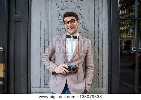 Smiling young man in funny round glasses holding old vintage photo camera