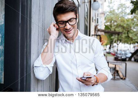 Happy young man in glasses listening to music from mobile phone on the street of the city