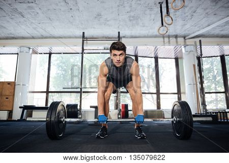 Young athlete wearing sportswear lifting big barbell at gym