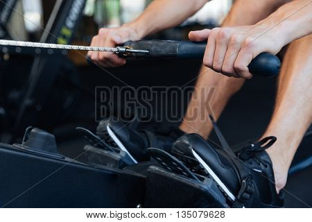 Cropped image of a fitness young man using rowing machine in the gym
