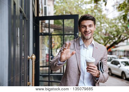 Young business man drinking a cup of coffee and waving to someone outdoors at cafe
