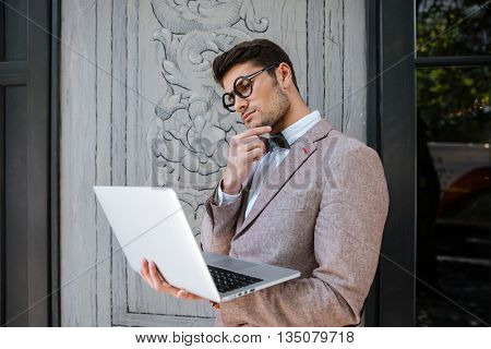 Thoughtful young man in funny round glasses thinking and using laptop