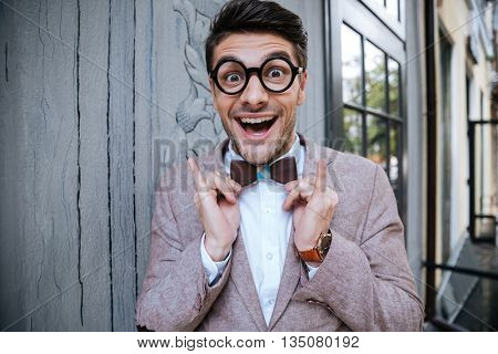 Portrait of cheerful funny young man in round glasses and wooden bowtie standing outdoors