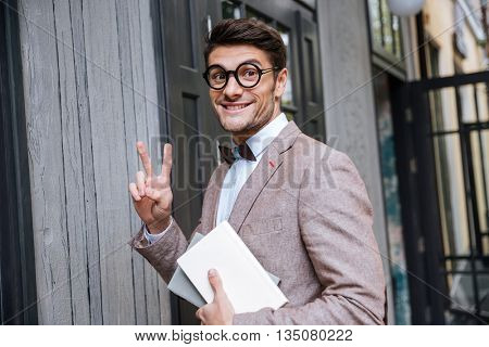 Young nerd man in eyeglasses making a face and showing v sign