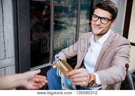 Cheerful young man sitting and paying by credit card in outdoor cafe