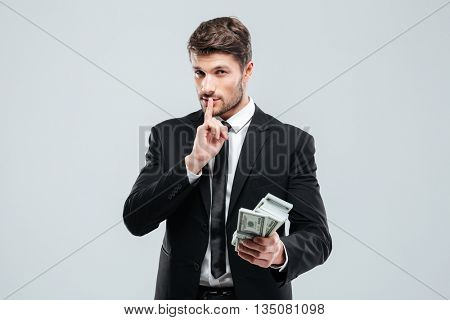 Handsome young businessman holding money and showing silence sign over white background