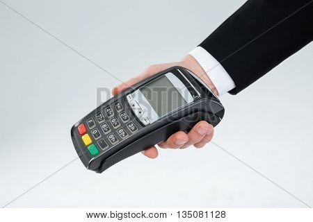 Closeup of hand of businessman holding payment terminal over white background