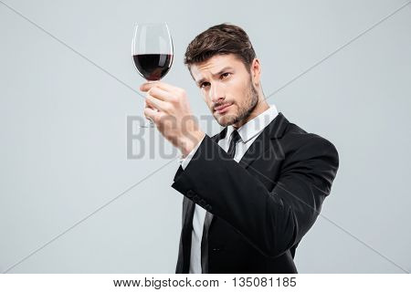 Concentrated young man sommelier tasting and looking at red wine in glass over white background
