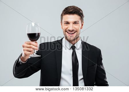 Cheeful young businessman smiling and drinking red wine over white background
