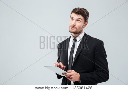 Portrait of pensive young businessman thinking and using tablet over white background