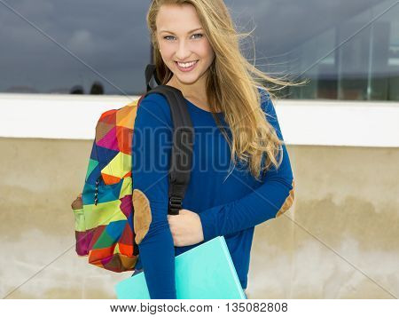 A beautiful student in the college holding a backpak and notebooks