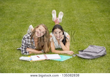 Tennage students lying on the grass and study together