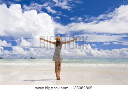 Beautiful woman on the beach enjoying the beauty of Praslin, Seychelles