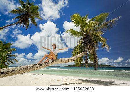 Beautiful woman sitting on a palmtree in La Digue, Seychelles