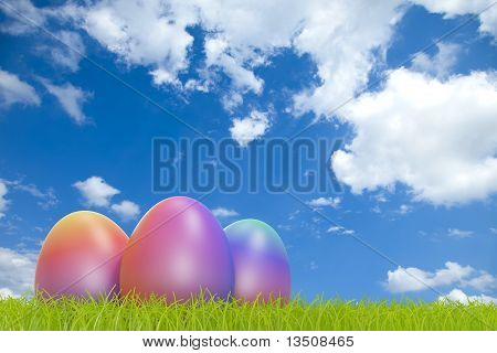 Rainbow colored easter eggs in front of a cloudy sky with COPYSPACE