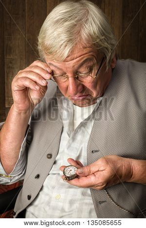 Elderly man checking the time on his antique pocket watch