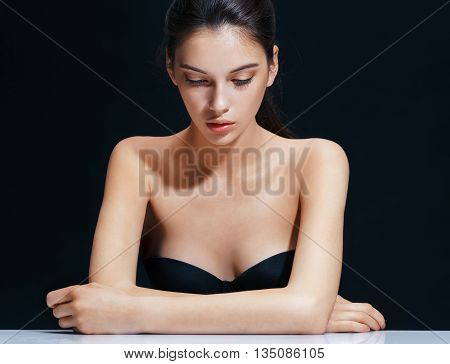 Beautiful brunette girl on black background. Close up attractive woman of european appearance. Youth and skin care concept