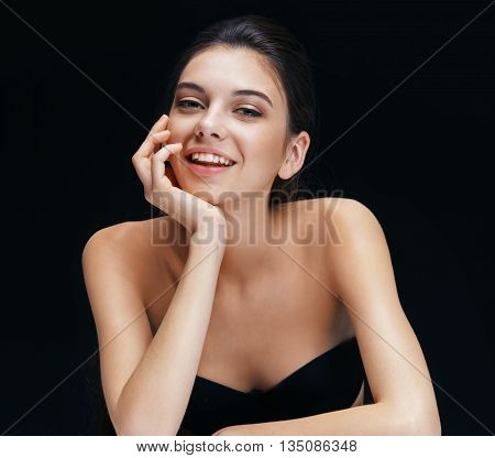 Charming young girl on black background. Photo of smiling brunette with perfect make up.