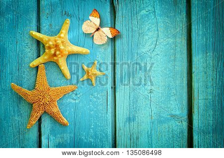 Summer beach. Starfish and butterfly on the blue wooden background.Summertime. Summer concept.