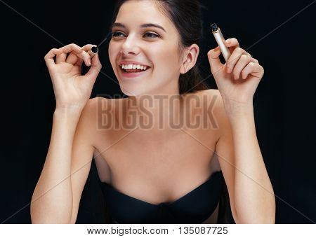 Beautiful young woman with mascara brush. Photo of smiling brunette girl on black background.