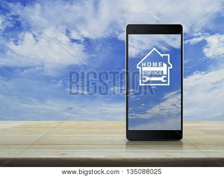 Hammer and wrench with house icon on modern smart phone screen on wooden table in front blue sky Home service concept