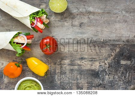 Mexican chicken fajita and ingrendients on a rustic wooden background