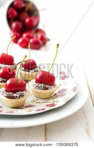 Delicious sweet chocolate tartlets with cherry on white wood
