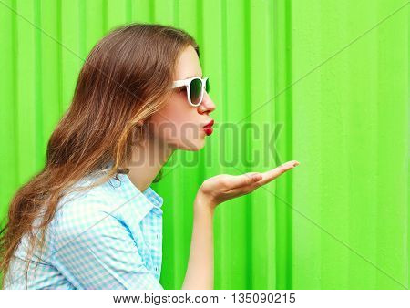 Woman In Sunglasses Sends An Air Kiss Over Colorful Green Backgr