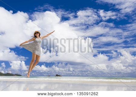 Beautiful woman jumping on the wonderful beach of Praslin, Seychelles