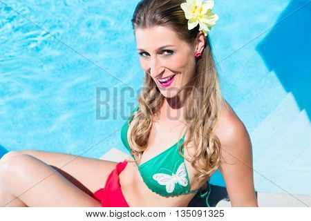 Woman relaxing at swimming pool in summer