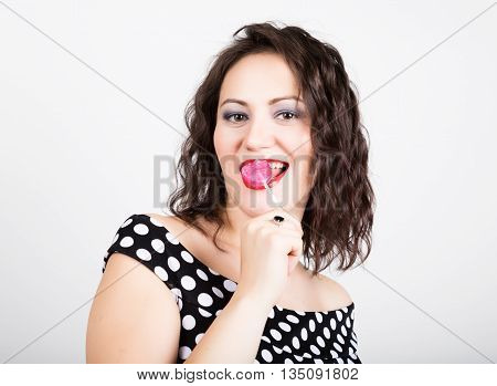 Portrait of happy beautiful young woman licking chupa chups. pretty woman with heart shaped lollipop.