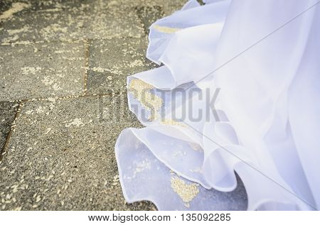 Detail of brides wedding dress with rice on the floor. Pavement full of rice after a wedding ceremony.