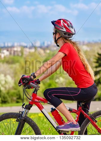 Unrecognizable bicycling girl. Girl rides bicycle into city. Cyclist is looking at city in distance. Girl returns from walk out of town.