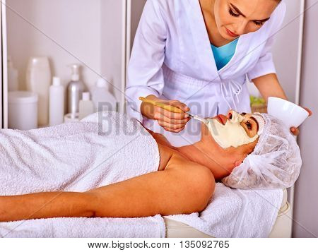Woman middle-aged lie on massage table take facial and neck clay mask in spa salon.