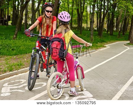 Bicycle girl wearing bicycle helmet and glass with rucksack ciclyng bicycle. Girls children cycling meet on white bike lane. Bicycle travel.
