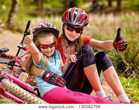 Bicycle family. Happy mother and daughter are sitting on road near bicycle and show thumb up. Bicycle racing concept.