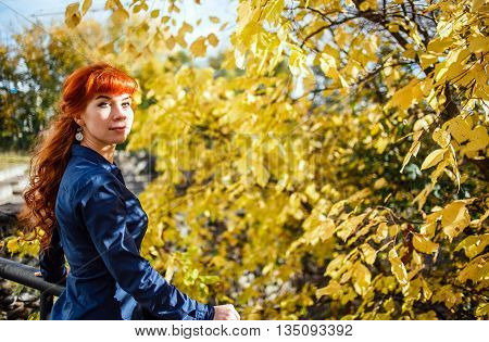 Beautiful woman in autumn park with yellow leaves background. Concept of autumn heat, positive energy, nature enjoy