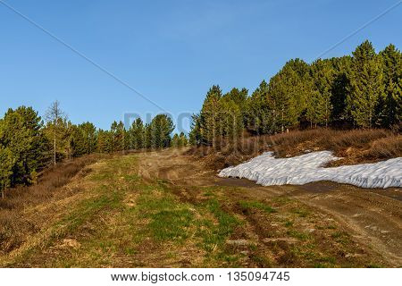Scenic view on dirt road up the mountain forest and snow at the side of the road on a sunny summer day
