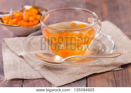 Tea with sea buckthorn on dark  wooden background