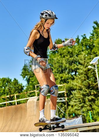Teen girl wearing skateboard helmet rides his skateboard outdoor. Girl do stunt aganist blue sky. Skateboard girl looks down.