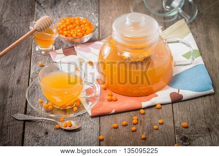 Tea with sea buckthorn and honey on wooden background