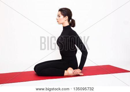 Beautiful athletic girl in black suit doing yoga. Virasana asana hero pose. Isolated on white background.