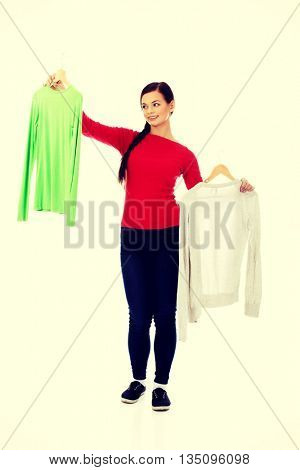 Smiling hesitant young woman holding two shirts