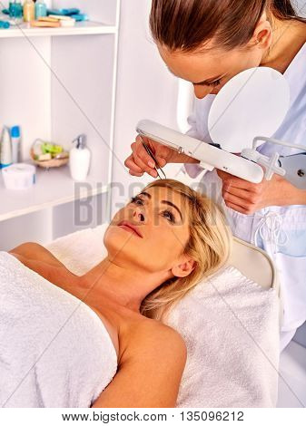 Woman middle-aged in spa salon with young beautician. Tweezing eyebrow by woman beautician.